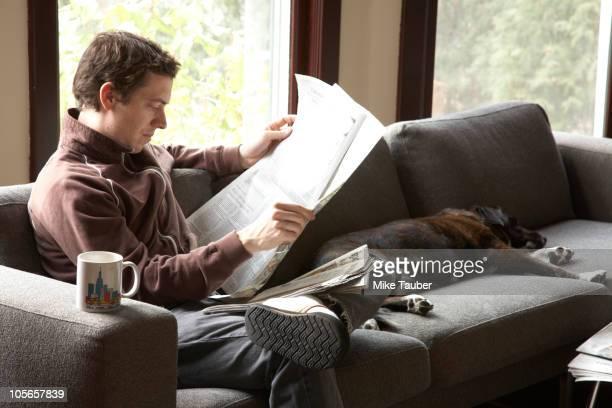 Caucasian man reading newspaper on sofa with dog
