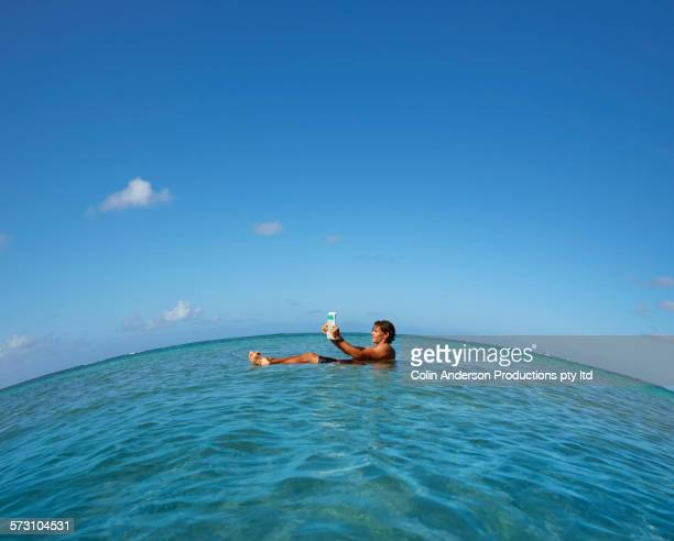 Caucasian man reading while floating in ocean