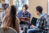 Caucasian man reads Bible with study group