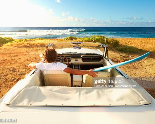 Caucasian man relaxing in convertible on beach
