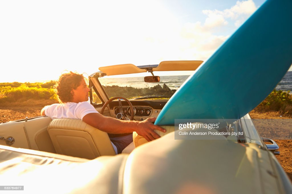 Caucasian man relaxing in convertible on beach : Foto stock
