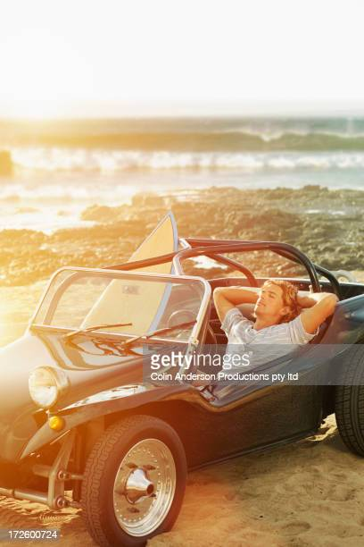 Caucasian man relaxing in jeep by beach