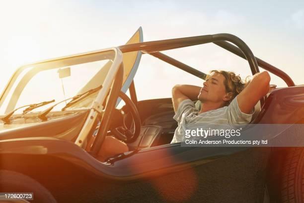 Caucasian man relaxing in jeep