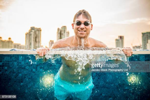 Caucasian man relaxing in urban rooftop swimming pool, Singapore