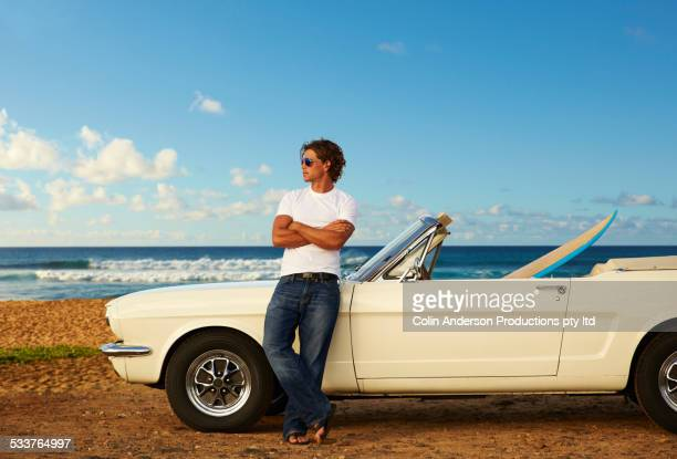 Caucasian man relaxing on convertible on beach