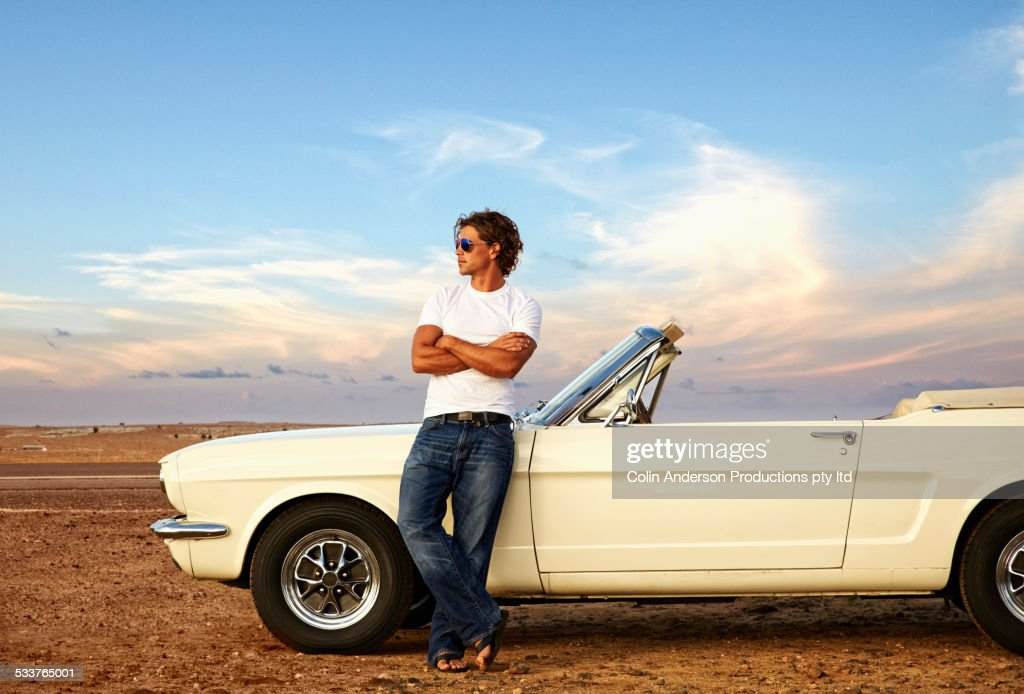 Caucasian man relaxing on convertible on remote road : Foto stock