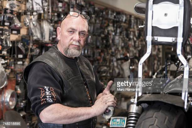 caucasian man repairing motorcycle and wiping hands - one mature man only stock photos and pictures