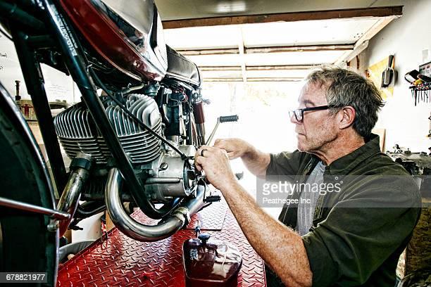 Caucasian man repairing motorcycle in garage