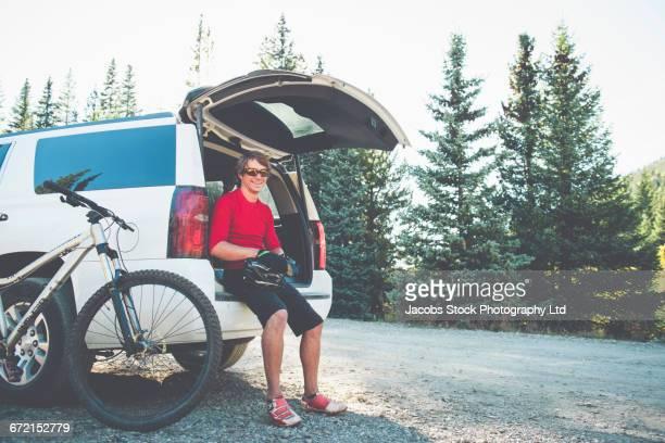 Caucasian man resting in car hatch near mountain bike