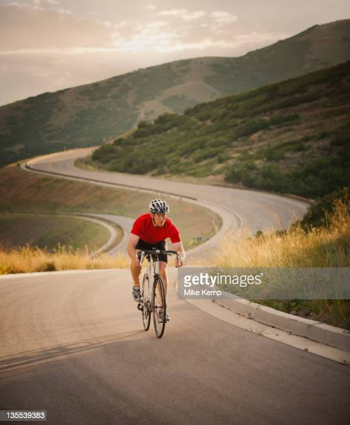 Caucasian man riding bicycle on remote road