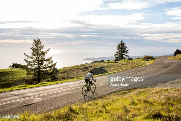 caucasian man riding bicycle on road near ocean - oakland california stock photos and pictures