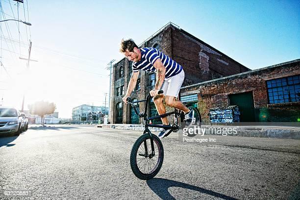 caucasian man riding bmx bike on street - bmx cycling stock pictures, royalty-free photos & images