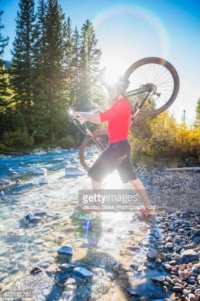 Caucasian man riding carrying mountain bike across stream