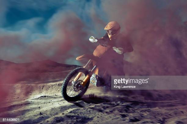 Caucasian man riding dirt bike in dust cloud