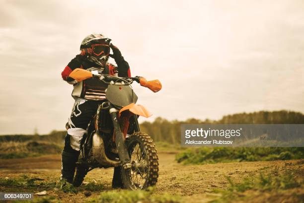 Caucasian man riding dirt bike in field