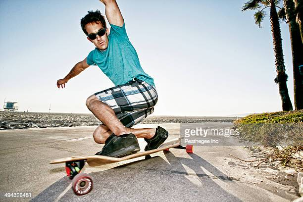 Caucasian man riding longboard on beach