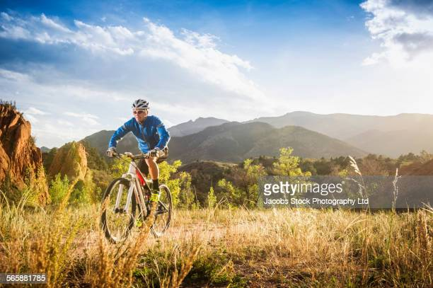 Caucasian man riding mountain bike in remote field