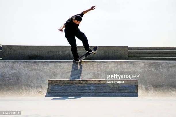 caucasian man riding skateboard in skate park - patinar fotografías e imágenes de stock