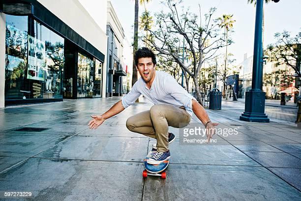 Caucasian man riding skateboard