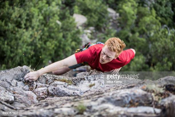 caucasian man rock climbing - rock wall stock pictures, royalty-free photos & images