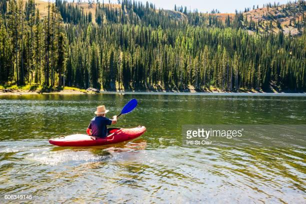 Caucasian man rowing canoe on remote lake