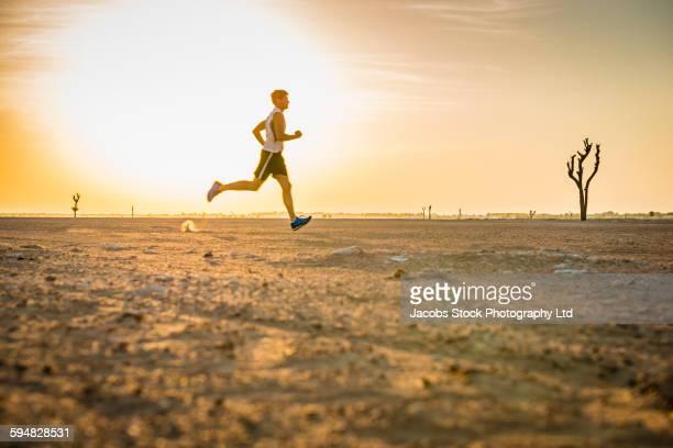 Caucasian man running in desert