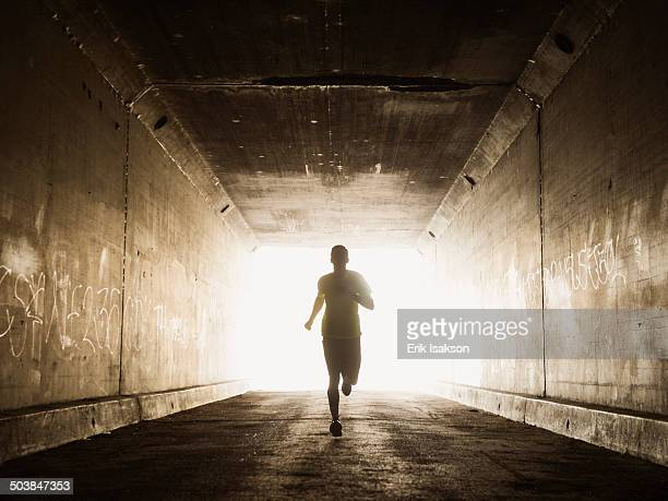caucasian man running in urban tunnel - back lit stock pictures, royalty-free photos & images
