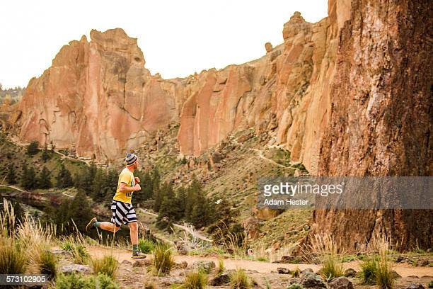 Caucasian man running near desert hills, Smith Rock State Park, Oregon, United States