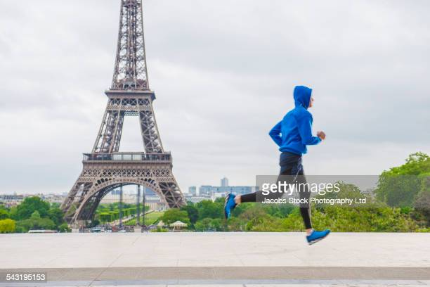 Caucasian man running near Eiffel Tower, Paris, France
