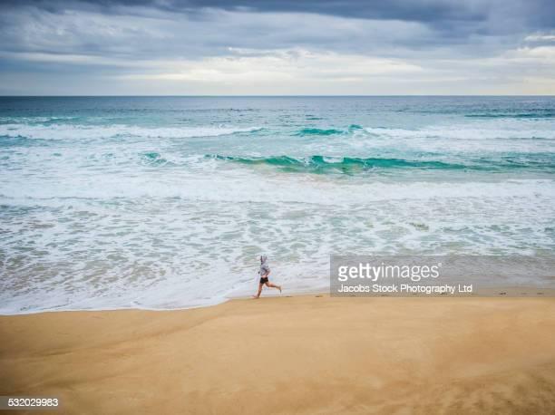 Caucasian man running near ocean waves on beach