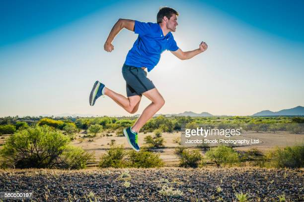 caucasian man running on remote road - running shorts stock pictures, royalty-free photos & images