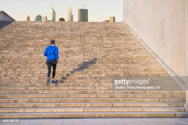 Caucasian man running up staircase