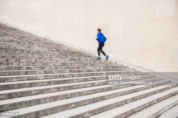 caucasian man running up staircase - escadaria - fotografias e filmes do acervo