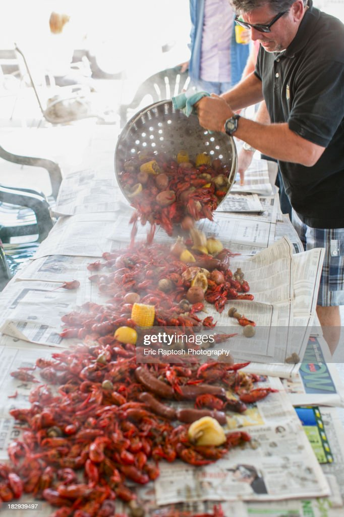 Caucasian man serving crawfish at boil : Stock Photo