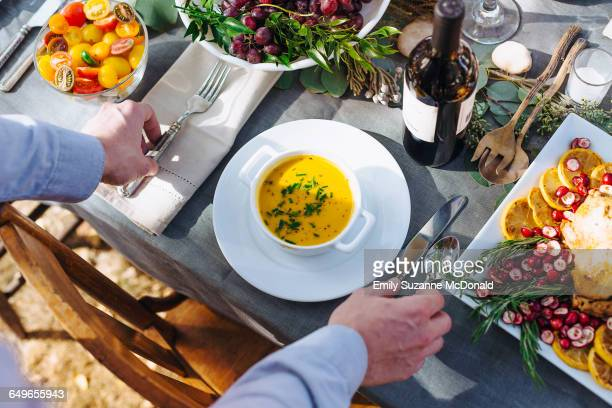 caucasian man setting platter of soup on outdoor table - farm to table stock photos and pictures
