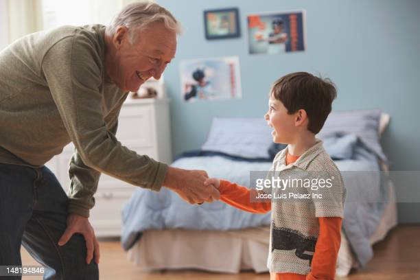 caucasian man shaking grandson's hand - bending stock pictures, royalty-free photos & images