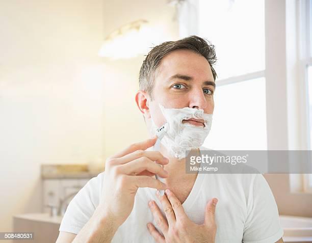 Caucasian man shaving in bathroom
