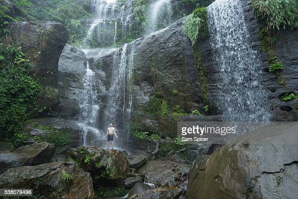 caucasian man showering in huge jungle waterfall - homme sous la douche photos et images de collection