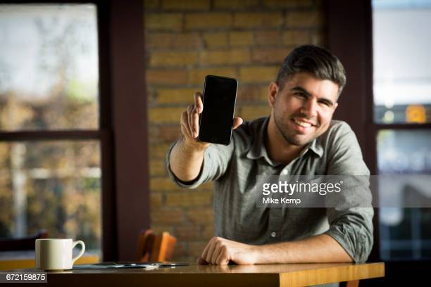 caucasian man showing cell phone in cafe - tonen stockfoto's en -beelden