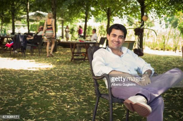Caucasian man sitting in chair in backyard