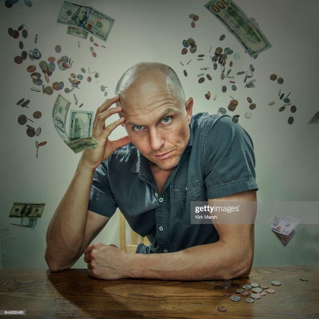 Caucasian man sitting in falling money : Stock Photo