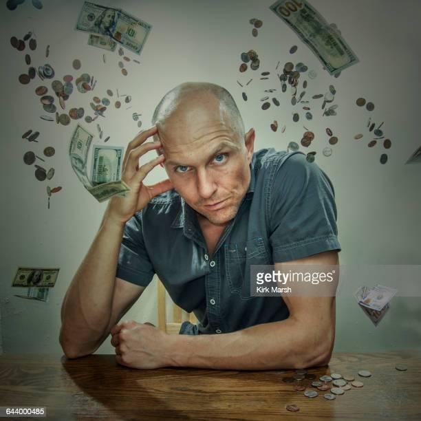 Caucasian man sitting in falling money