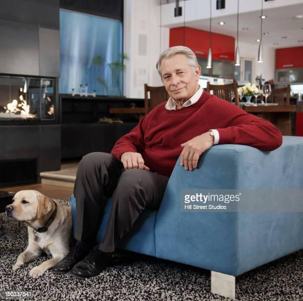 Caucasian man sitting in living room with dog