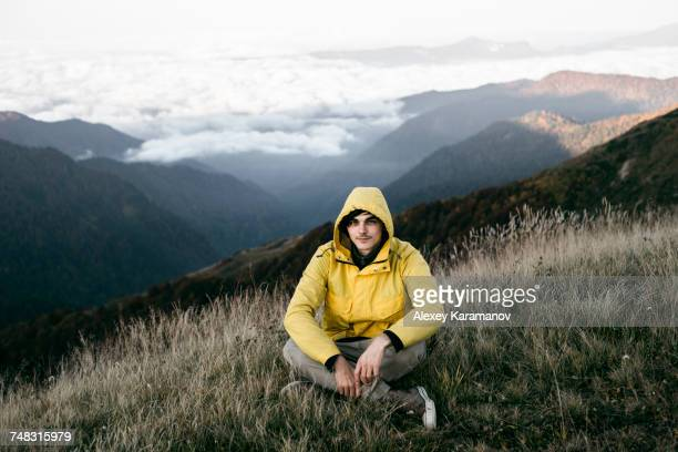 Caucasian man sitting in remote mountain landscape