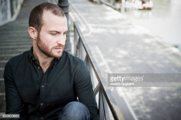 Caucasian man sitting on outdoor staircase