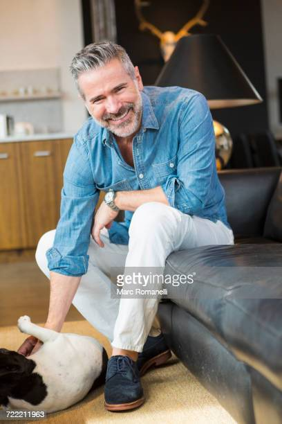 caucasian man sitting on sofa petting dog - suede shoe stock pictures, royalty-free photos & images