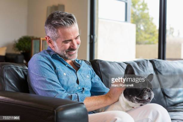 Caucasian man sitting on sofa petting dog