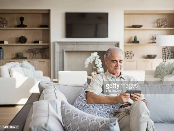 caucasian man sitting on sofa texting on cell phone - one man only stock pictures, royalty-free photos & images