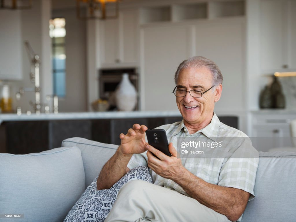 Caucasian man sitting on sofa texting on cell phone : Stock Photo