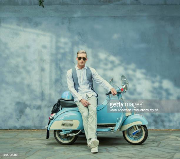 caucasian man sitting on vintage scooter - fidanzato foto e immagini stock